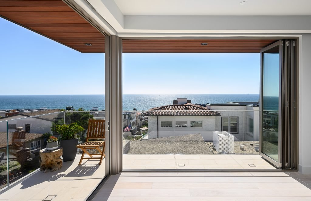 ocean view from luxury home with hardwood flooring and glass windows